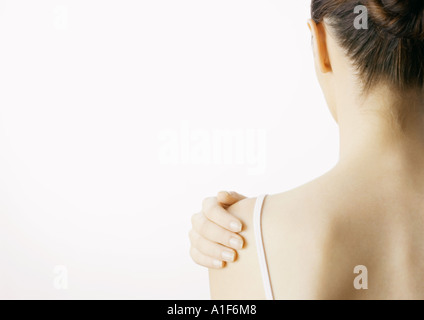 Woman with hand on shoulder, rear view - Stock Photo