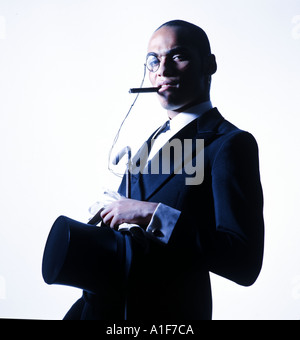 Young black man with monocle, cigar and tailcoat outfit looking very self-confident in to the camera - Stock Photo