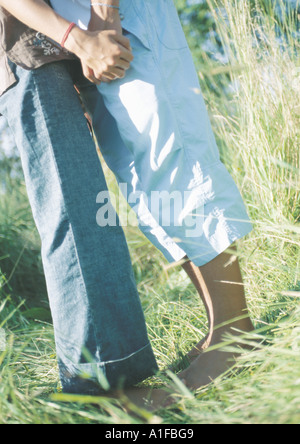 Young couple standing in grass, holding hands - Stock Photo