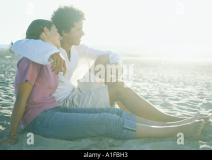Teenage couple sitting on beach - Stock Photo