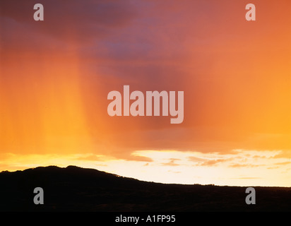 Sunset colored streaky rainclouds from a thunderstorm near Cimarron Colorado - Stock Photo