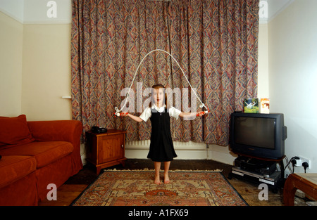 A girl playing with a skipping rope indoors - Stock Photo