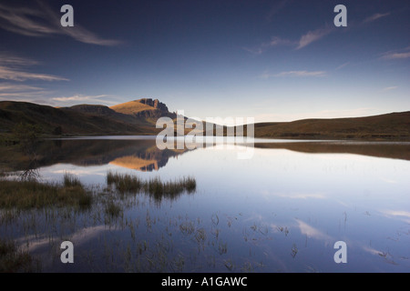 The Old Man of Storr rock pinnacle reflected in still loch on Isle of Skye - Stock Photo