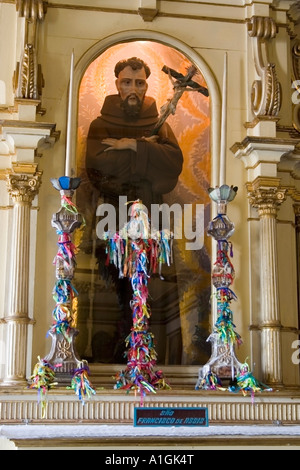 Statue of Saint Francis crucifix and chandeliers covered with Senhor do Bonfim ribbons Salvador da Bahia Brazil - Stock Photo