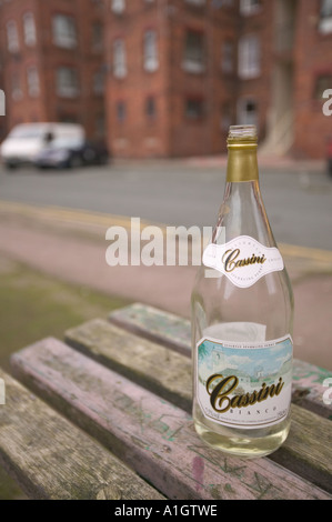 a cheap bottle of wine abandoned by a street drinker amongst tenement flats on Barrow Island, Barrow in Furness, - Stock Photo