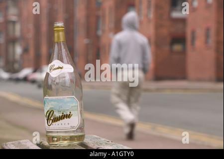 a hoody wearing youth walks past an abandoned wine bottle on Barrow island, Barrow in Furness, Cumbria, UK - Stock Photo
