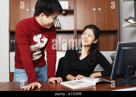 Young man standing with a mid adult woman sitting beside him smiling - Stock Photo