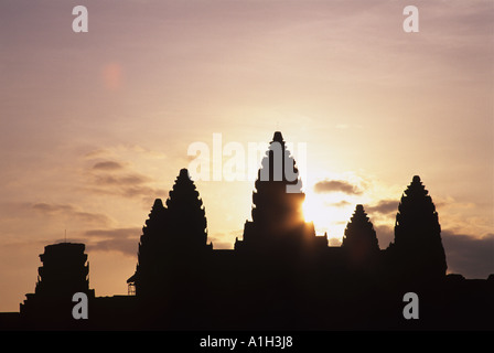 Angkor Wat in Cambodia seen here at at sunrise is a temple complex and the largest religious monument in the world - Stock Photo