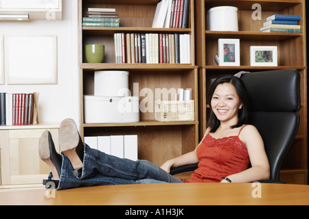 Portrait of a businesswoman sitting with her legs on the table - Stock Photo