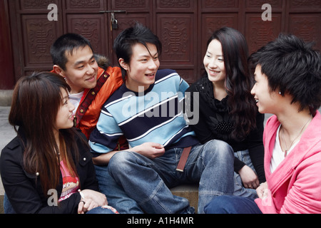 Two young men talking to two young women and a teenage boy - Stock Photo