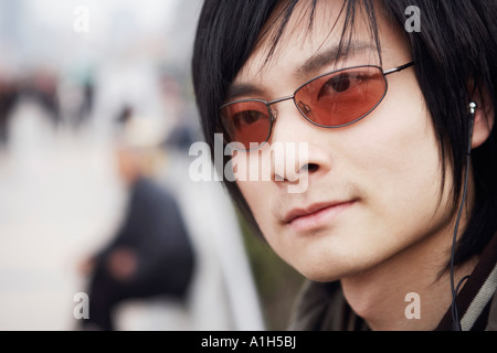 Close-up of a young man wearing headphones - Stock Photo