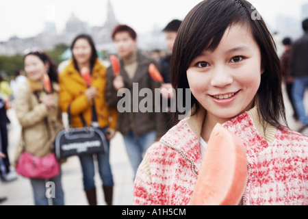 Portrait of a young woman holding a watermelon - Stock Photo