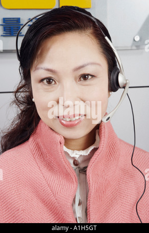 Portrait of a mature woman wearing a headset - Stock Photo