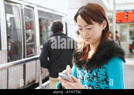 Side profile of a young woman operating a mobile phone with a digitized pen - Stock Photo