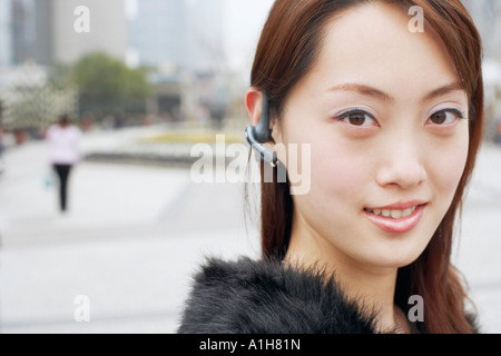 Portrait of a young woman wearing a hands free device - Stock Photo