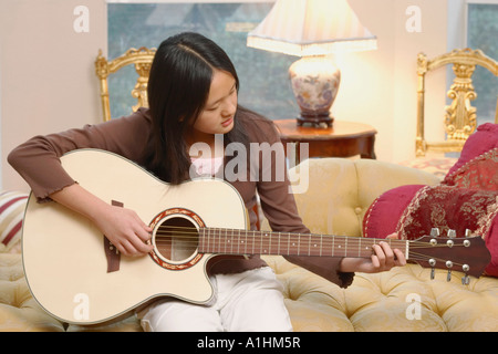 Close-up of a girl playing the guitar