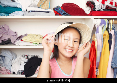 Portrait of a girl holding a hat on her head - Stock Photo