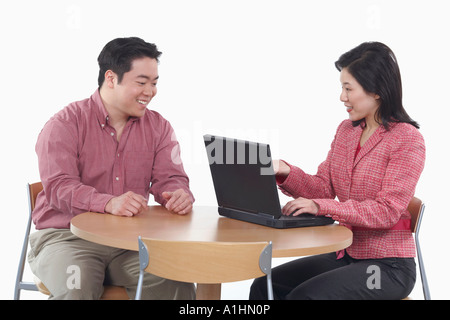 Close-up of a businesswoman and a businessman smiling - Stock Photo