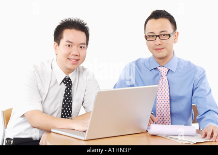 Portrait of two businessmen sitting in front of a laptop - Stock Photo