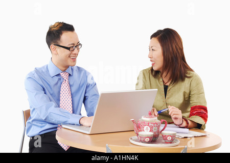 Close-up of a businessman and a businesswoman in front of a laptop - Stock Photo