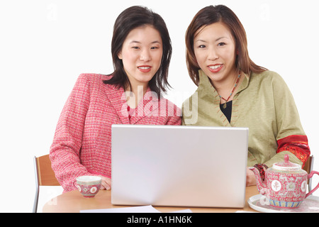 Portrait of two businesswomen using a laptop - Stock Photo