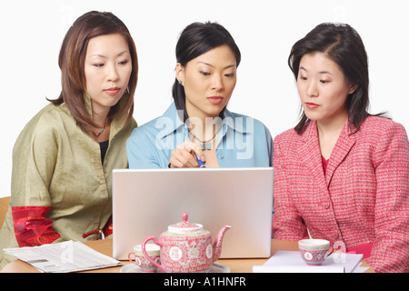 Close-up of three businesswomen in front of a laptop - Stock Photo