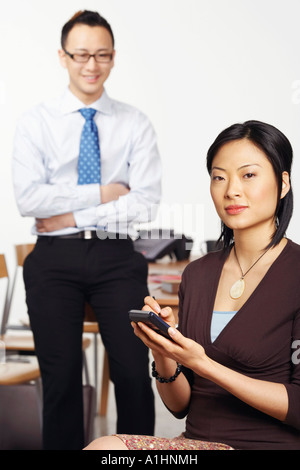 Portrait of a businesswoman holding a personal data assistant with a businessman standing behind her - Stock Photo