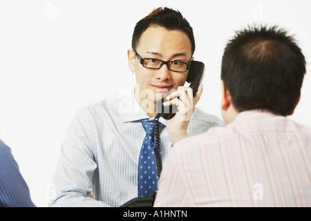 Portrait of a businessman talking on the telephone with two businessmen sitting in front of him - Stock Photo