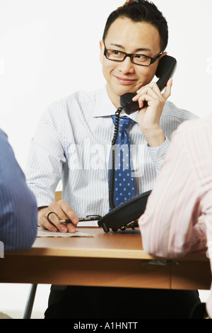 Close-up of a businessman talking on the telephone with two businessmen sitting in front of him - Stock Photo