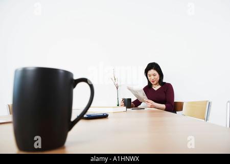 Businesswoman reading a newspaper - Stock Photo