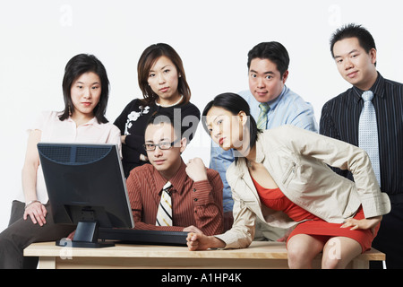 Portrait of a group of business executives in front of a computer - Stock Photo