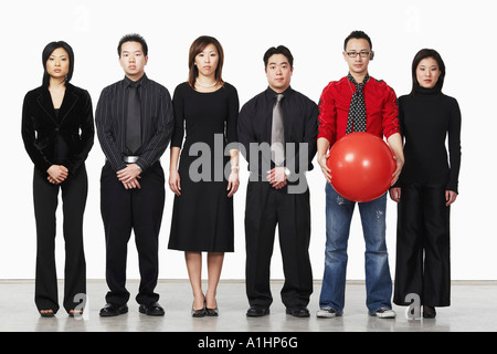 Portrait of a young man standing holding a ball with a group of business executives - Stock Photo