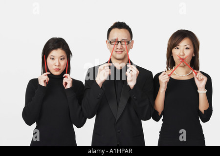 Two young women and a young man gesturing speak no evil, hear no evil, see no evil with chopsticks - Stock Photo
