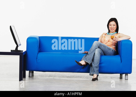 Young woman holding a glass of red wine sitting on a couch - Stock Photo