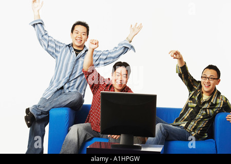 Close-up of three young men cheering in front of a flat screen monitor - Stock Photo