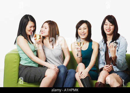 Close-up of four young women sitting on a couch smiling - Stock Photo