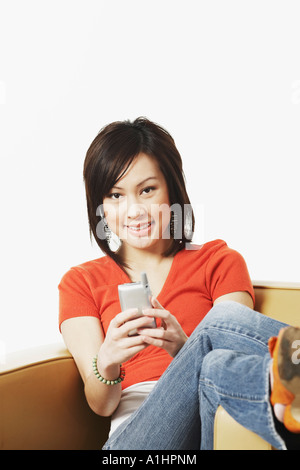 Portrait of a young woman operating a mobile phone - Stock Photo