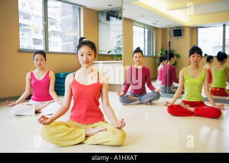 Four young women sitting in the lotus position - Stock Photo