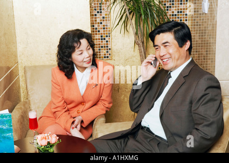 Businessman sitting with a businesswoman in a restaurant talking on a mobile phone - Stock Photo