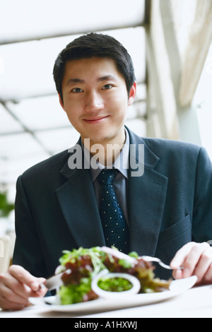 Portrait of a businessman seated at the table in a restaurant smiling - Stock Photo