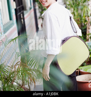 Portrait of a young man carrying a bag and smiling - Stock Photo