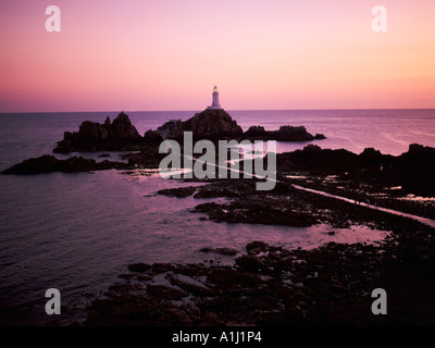 La Corbiere lighthouse at sunset linked to the Jersey mainland at low tide by a concrete causeway, - Stock Photo