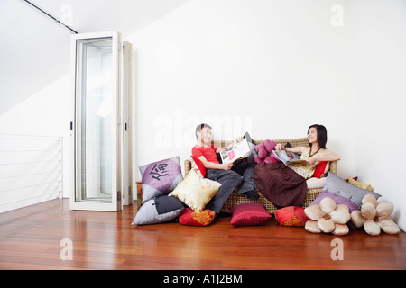 Side profile of a mid adult man with a young woman reclining on a couch and looking at each other - Stock Photo