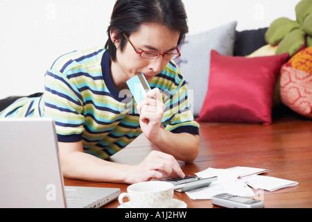 Mid adult man calculating bills using a calculator - Stock Photo
