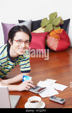 Portrait of a mid adult man calculating bills using a calculator - Stock Photo