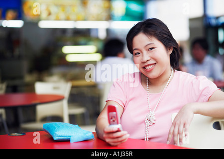 Portrait of a young woman sitting at a sidewalk cafe and holding a mobile phone - Stock Photo