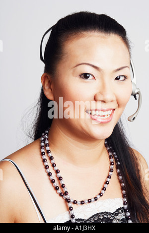 Portrait of a young woman smiling and wearing a headset - Stock Photo