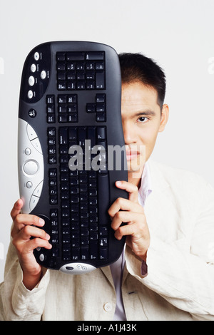 Portrait of a businessman holding a computer keyboard in front of his face - Stock Photo