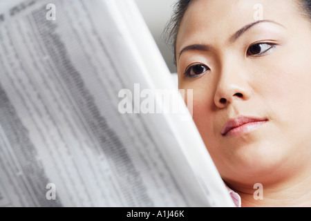 Close-up of a businesswoman reading a financial newspaper - Stock Photo