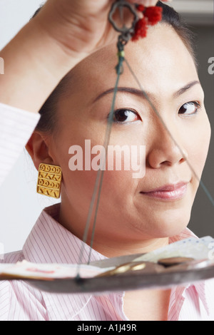 Portrait of a businesswoman weighing paper currency with coins on a weighing scale - Stock Photo